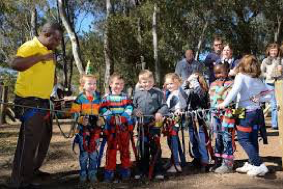 A group of kids are getting all strapped up and ready to do some swinging through the trees at Acrobranch.  The kids are posing for a photo in their harnesses