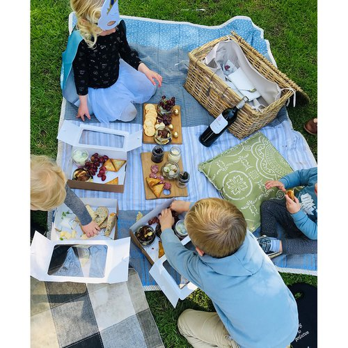 Children sitting on a blue blanket eating cheese and biscuits at Delheim Winery. Kids wearing maskd having fun at a picnic on the grass.
