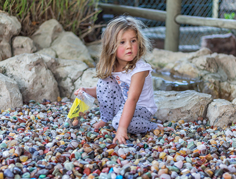 This picture shows a little girl sittingin a scrach patch of stones. There are hundreds of colourful stones underneath her.