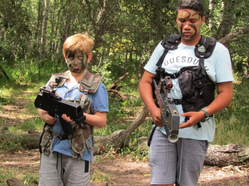 Boys in a forest holding laser guns and ready for a fight.  They have the trees and bushes surrounding them.