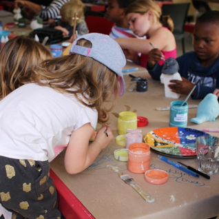 a bunch of children sitting at a table making crafts from clay.  There are a lot of open bottles of paint and in all sorts of colours