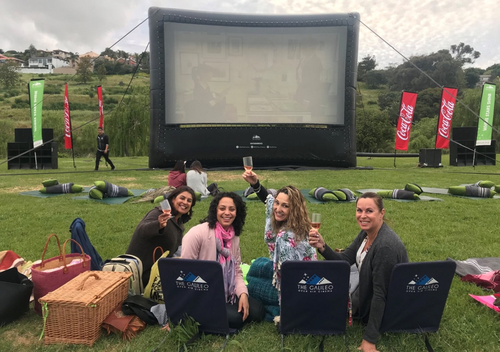 A group of woman toasting to their outdoor movie at the Galileo outdoor cinema. Theyre sitting on Galileo branded chairs in an open wine farm.
