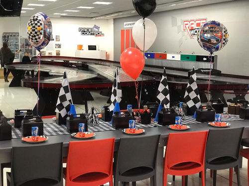 The picture shows the race track and an example of a race car party set up.  There are ballons and checkered flags and slot car racing.