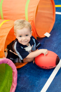 A little boy is holding a rugby ball as he crawls through a tunnel. Fun, structured ball skills for children with rugby tots