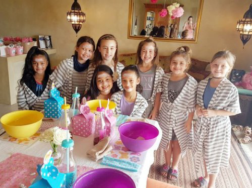 A group of little girls posing for a photo in front of their pamer table.  They're all wearing gowns and have face masks on
